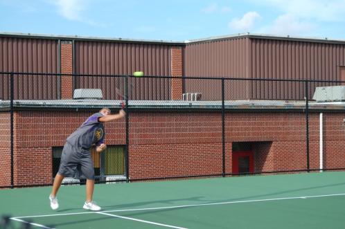 Senior Jacob Tuell returning a serve at the varsity tennis match