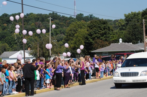 Cornwell's students release balloons as the funeral procession passes on Elm Street on the way to the Community Cemetery for her burial.