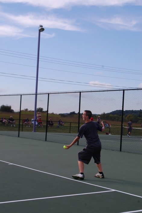 Junior Jeff Kenney tosses a ball for his serve.