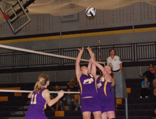 Two seventh graders work together to send the ball over the net.