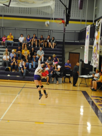 Freshman Claire Cornwell serves the ball over the net.