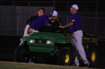 Coaches Lee Wrobleski and Billy Vincent surround the gator while giving Mrs. B a hug after the big win against Corydon Central.