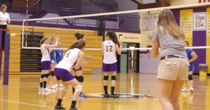 Coach Bough coaches the girls while Shoals is serving the ball.