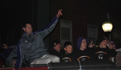 Coach Matt Holcomb celebrates with the team as they return from the sectional championship game.