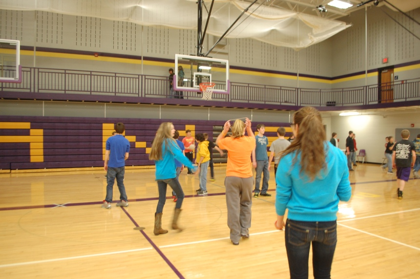 A group of junior high boys and girls play volleyball and basketball during junior high lunch/recess in the auxiliary gym.