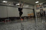 Sophomore Tyler Pavey does a one-handed cartwheel during his dance in color guard practice.