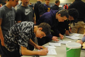 Several eighth graders fill out surveys for the Reality Fair.