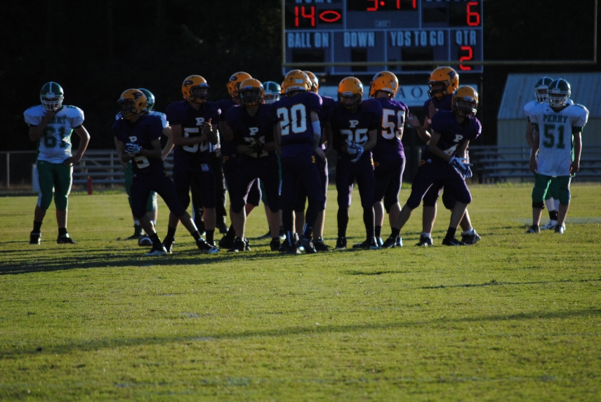 The JV football team breaks the huddle and run a play in their win against Perry Central.