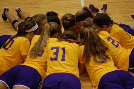 The eighth grade girls get ready before their game by praying.