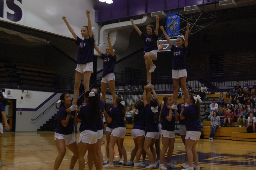The Varsity and JV cheer team do their ending pose at the end of their performance to the song.