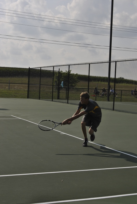 Senior Kyle Street gets low to hit the ball back during a tough match.