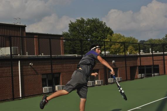 Senior Mason Deaton hits the ball back during a home tennis match.