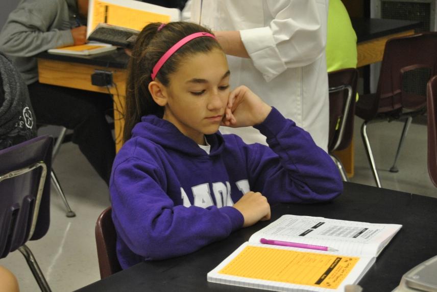 Eighth grader Kaylee Schneider listens to her science teacher to know what to do.