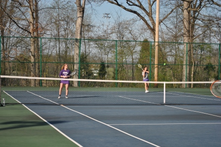 Seniors working together to hit the ball back, during a tennis match against Forest Park.