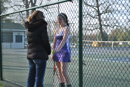 Freshmen Emma Osborn, talking to coach before her tennis match.